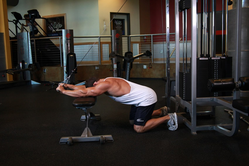 extensiones de tríceps en polea con rodillas apoyadas en el suelo